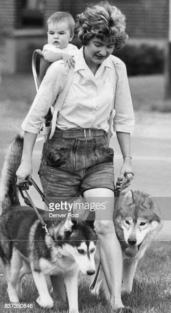 Mom Has Her Hands Full Mrs Richard Reed of 1655 S Holly St and her daughter Tracy 7 months take the family dogs for a walk along S Holly St Dogs are...