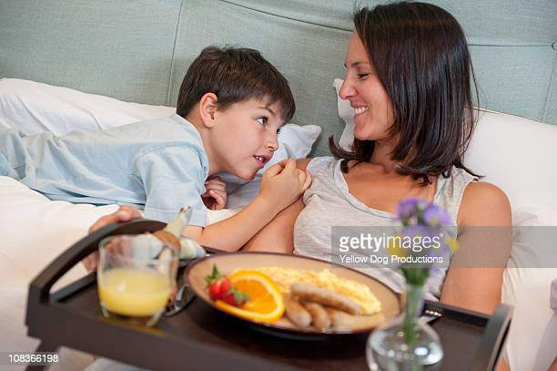 Mom having breakfast in bed with her son