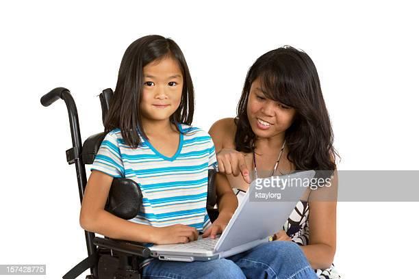 Mom helping daughter use laptop