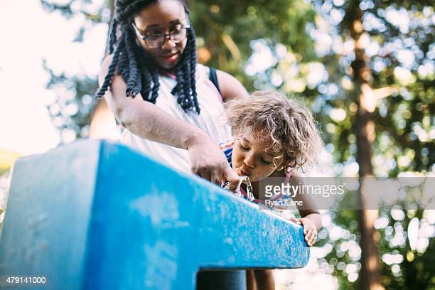 Mom Helps Daughter at Public Drinking Fountain