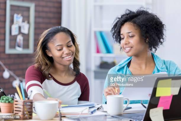 Mom helps teenage daughter with homework