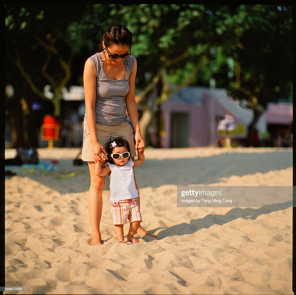 Mom holding Baby in shade standing on beach : Stock Photo