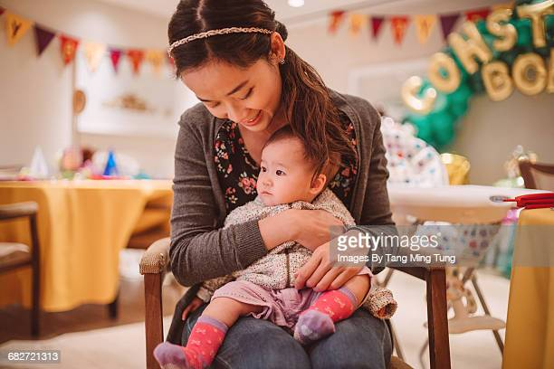 Mom holding baby joyfully in a party