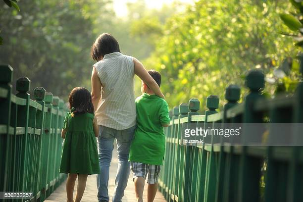 Mom holding taking a stroll with her children