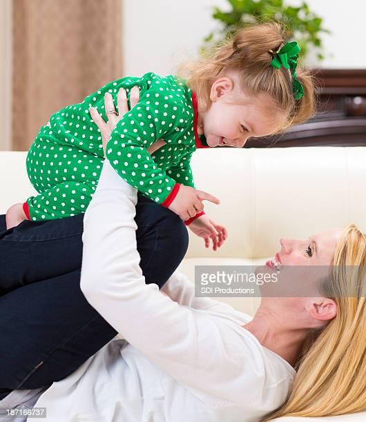 Madre tenendo la figlia bambino e ridere a Natale