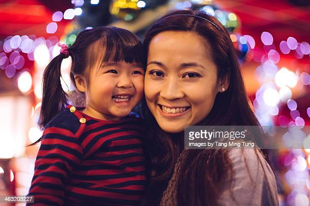 Mom holding toddler girl smiling joyfully