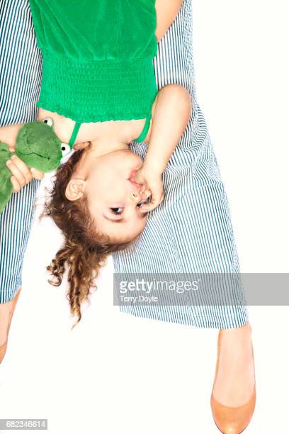mom holding young girl upside down with her thumb in her mouth
