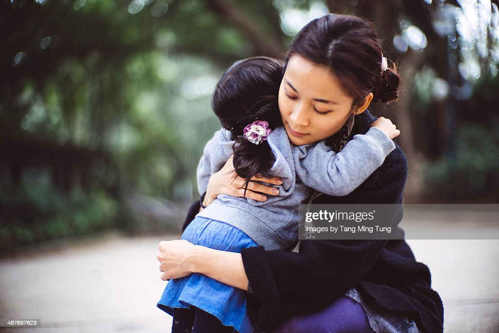 Mom hugging toddler girl in the park : Stock Photo