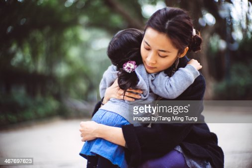 Mom hugging toddler girl in the park : Stock Photo