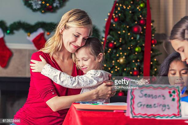 Mom hugs daughter while making Christmas cards