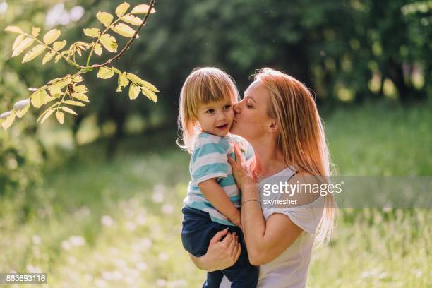 mom is kissing her son in nature