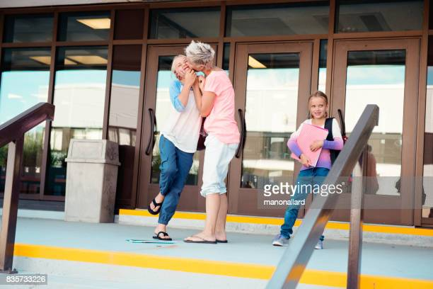 Mom kisses her little girl who is back at school