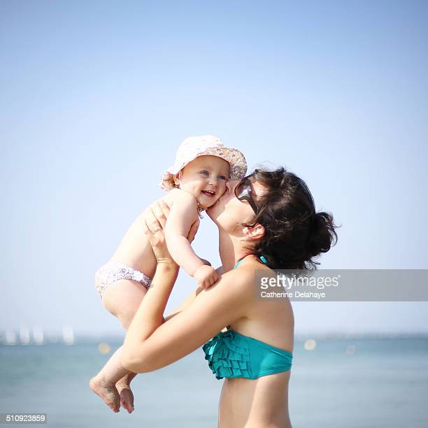 A mom kissing her baby girl on the beach