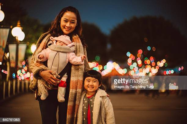 Mom &  little daughters smiling at camera at night