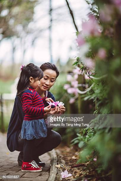 Mom & little girl admiring flowers in park