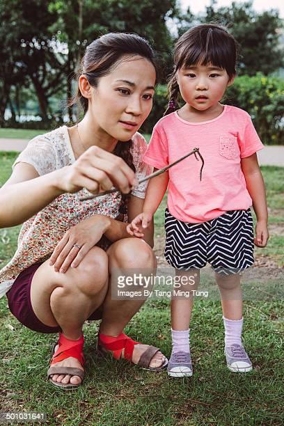 Mom & little girl examining earthworm with mom