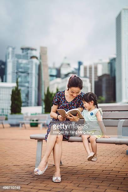 Mom & little girl reading book in city