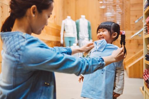 Mom & little girl shopping kid's wear in shop