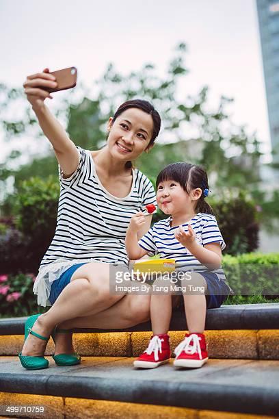 Mom & little girl taking selfie in park joyfully