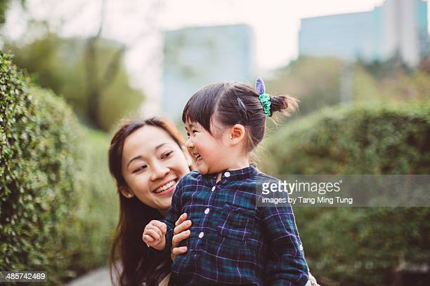 Mom & little girl talking joyfully in park