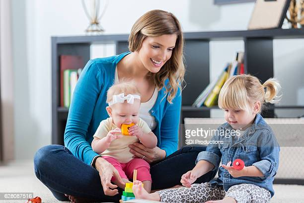 Mom or nanny plays with children at home