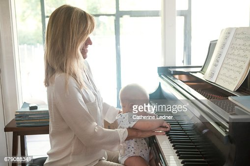 Mom playing grand piano with baby