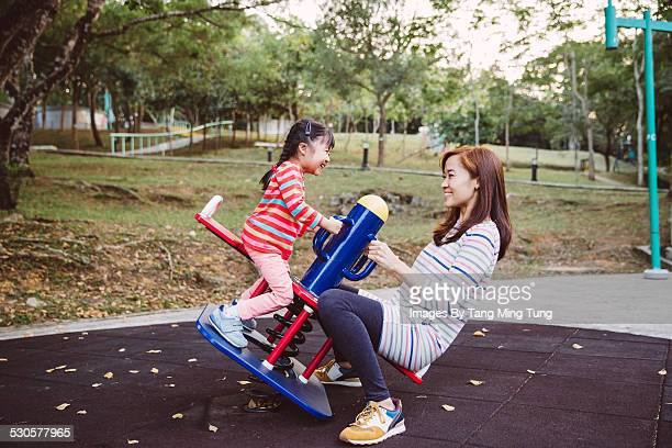 Mom playing seesaw with daughter in playground