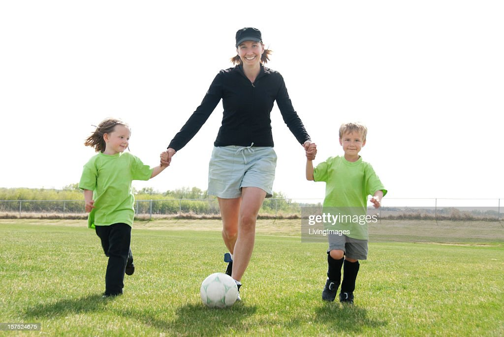 A mom playing soccer with her two children
