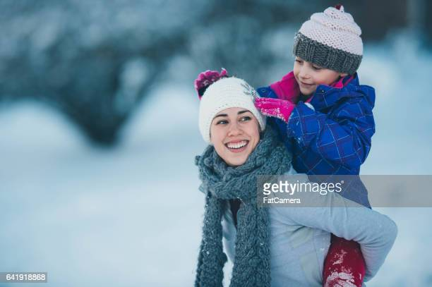 Mom Playing With Young Daughter in Snow