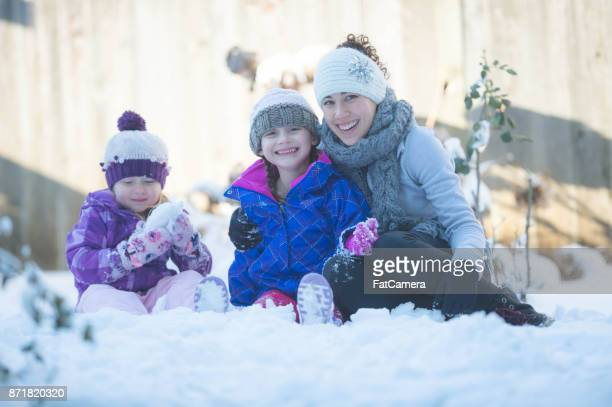 Mom Playing With Young Girls on Snowy Neighborhood Street