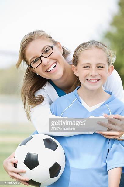 Mom posing with daughter before soccer game
