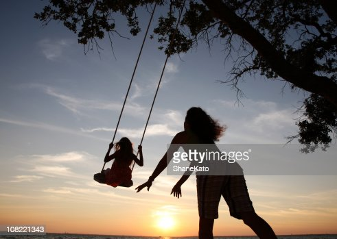 Mom pushes Daughter on swing set playing at sunset silhouette