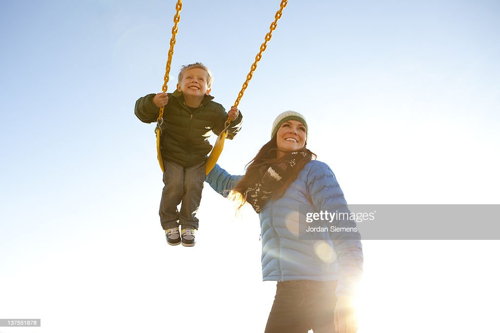 Mom pushing son on a swing set.