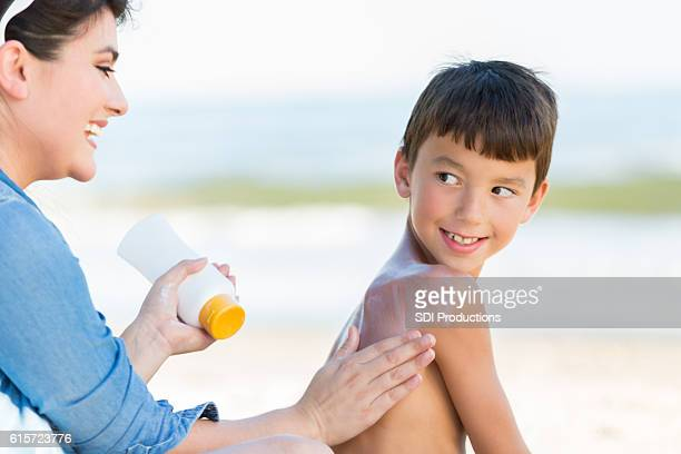 Mom puts sunscreen on son on the beach