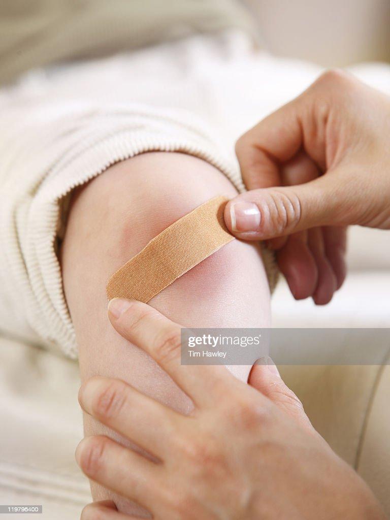 Mom putting bandage on skinned knee