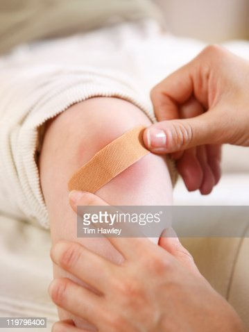 Mom putting bandage on skinned knee
