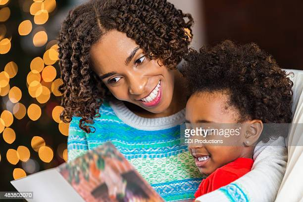 Mom reading Christmas card to daughter at home