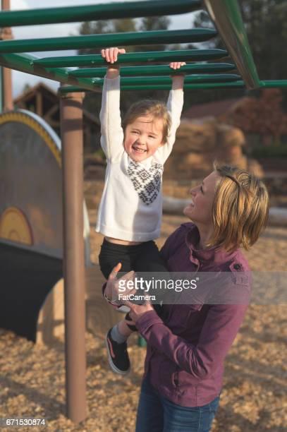 Manèges de maman vers le bas de la diapositive à l'aire de jeux avec sa jeune fille aide sa jeune fille apprendre à utiliser le monkeybars à la Cour de récréation