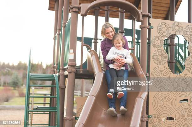 Mom rides down slide at playground with her young daughter