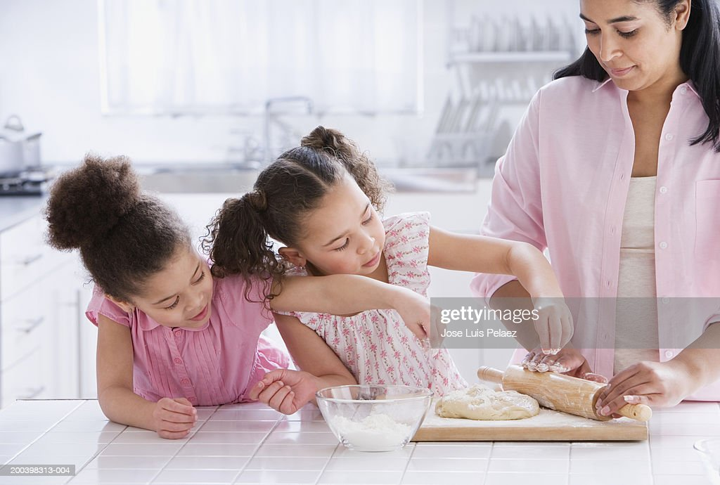 Mom rolling dough while two girls (4-6) pour flour : Stock Photo