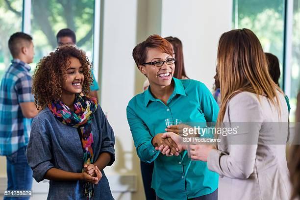 Mutter mit Tochter Hände schütteln der Lehrer während der Veranstaltung.