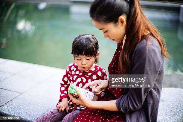 Mom showing a juice box packaging to toddler girl
