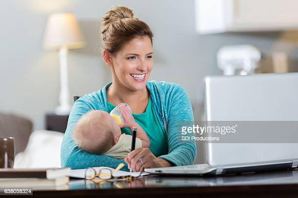 Mom studies while feeding her baby girl