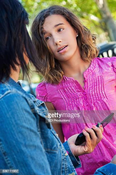 Mère tient téléphone portable de jeune fille