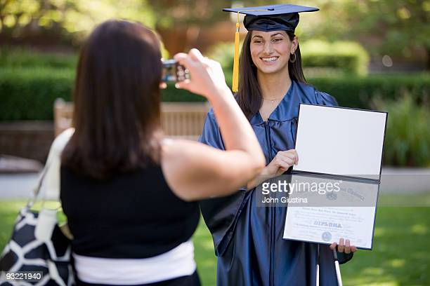 Mom taking a picture of her daughter with diploma.