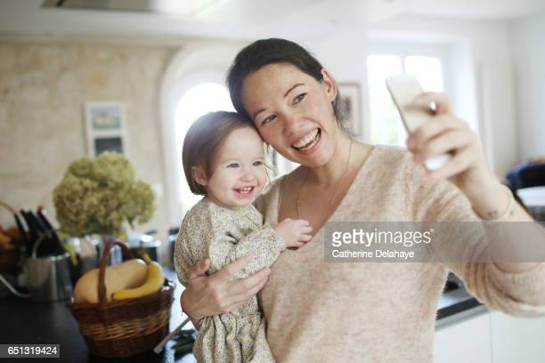 A mom taking a selfie with her little girl