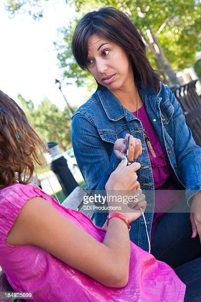 Mère prenant son téléphone cellulaire de jeune fille
