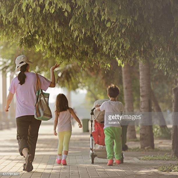 mom taking children on morning walk at the beach