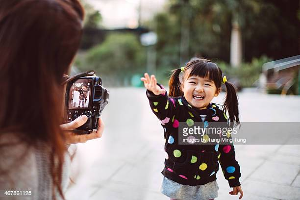 Mom taking picture for toddler girl in park