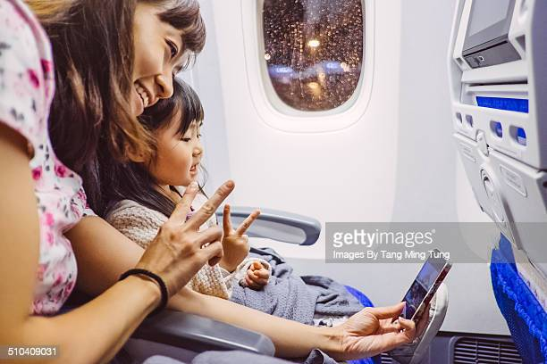Mom taking selfies with child in airplane